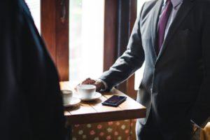 Deux hommes en costumes autour d'une table avec deux cafés et un téléphone.