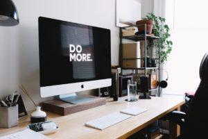 """Un bureau avec un ordinateur avec un écran noir et écrit en blanc en grosse lettre : """"Do more"""""""