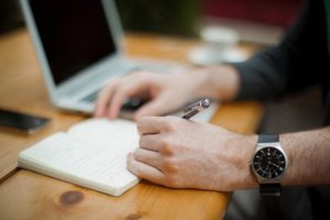 Un homme ecrit sur un bloc-note à côté d'un ordinateur.