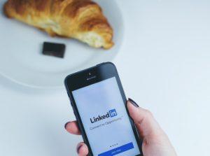 Main de femme tenant un smartphone sur la page de LinkedIn. À côté il y a une assiette avec un croissant et du chocolat dessus.