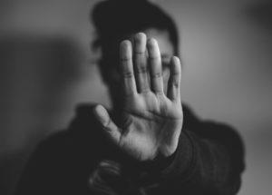 Photo noir et blanc d'une femme qui étend sa main devant son visage comme pour dire stop ou non.