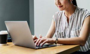 Femme assise à une table devant son ordinateur en souriant