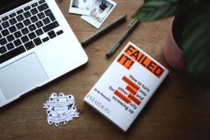 Une table vue de haut avec un ordinateur et un livre expliquant comment transformer ses échecs en réussites.