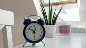Un réveil ancien sur une table blanche à côté d'une bougie et d'une plante.