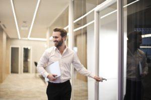 Un homme en chemise blanche sourit. Il est dans un couloir et il s'apprête à ouvrir une porte.