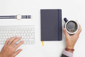 Un bureau blanc avec un clavier, une montre, un bloc-note et une main qui tient une tasse de café.