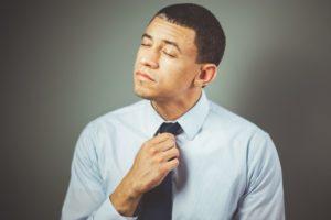 Un homme ferme les yeux et et réajuste sa cravate.