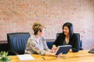 Deux femmes assises à une table dans un cadre professionnel. Elles discutent et semblent être en pleine réunion.
