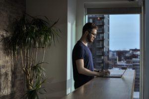 Une homme debout devant une table avec un ordinateur portable en face de lui. Il se tient devant une grande baie vitrée d'où l'on voit des immeubles. Il y a une plante derrière lui.