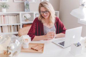 Une femme souriante est assise à une table devant son ordinateur avec une tasse de thé à la main.