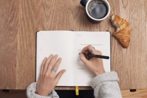 Une femme écrit dans son journal à côté d'un café et d'un croissant.