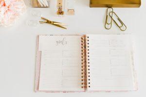 Un agenda ouvert sur une table blanche avec des fournitures dorées autour.