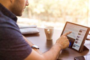 Un homme assis à une table devant une tablette avec une tasse de café.