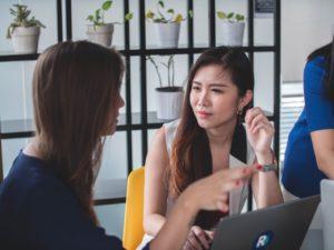Deux collègues faces à un ordinateur se regarde. L'une d'entre elle à l'air confuse par ce que l'autre lui dit.