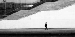 Un homme marche devant un bâtiment avec un grand escalier, à l'entrée. La photo est en noir et blanc.