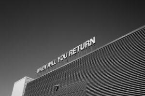 """Photo en noir et blanc d'un signe en haut d'un immeuble : """"When will you return"""""""