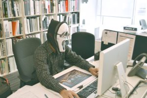 Un homme assis à un bureau devant un ordinateur. Il porte le masque de Scream.