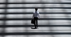 Un homme marche dans la rue en tenant un attaché-case.