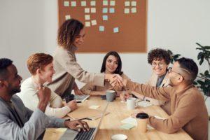Un groupe de personnes assises autour d'une table. Une femme est debout et serre la main à un homme assis en face d'elle.