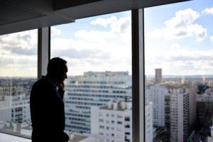 Un homme de dos devant une fenêtre donnant sur une ville avec des gratte-ciels. Il est au téléphone.
