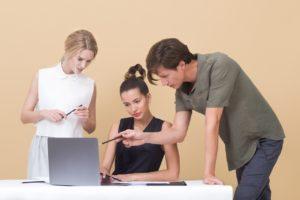 Un homme et une femme commente le travail d'une personne assise à son ordinateur.