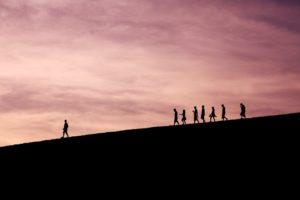 Un groupe d'individu suit une personne sur une colline.