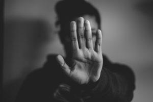"""Une photo en noir et blanc où l'on voit une femme mettre sa main en avant comme pour dire """"stop"""". Sa main cache son visage."""