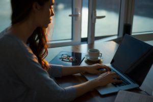 Une femme assise à une table près d'une fenêtre. Elle tape sur un ordinateur portable. À côté d'elle, il y a un mug, un carnet et des lunettes de vue.
