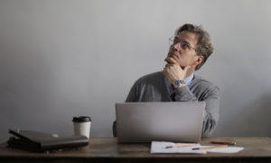 Un homme assis à une table devant un ordianteur portable et un café. Il a l'air pensif ; il a une main sous son menton et regarde le plafond.