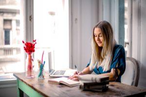 Une femme blonde avec une chemise bleue est assise à son bureau devant une fenêtre. Elle feuillette un carnet.