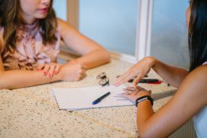 Deux femmes assises à une table se font face. Sur la table il y a un papier, un stylo et des lunettes de vues. On ne voit que la table et leurs mains.