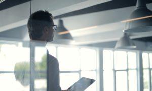 On voit un homme de dos à travers une vitre. Il tient une tablette et il semble mener une présentation.