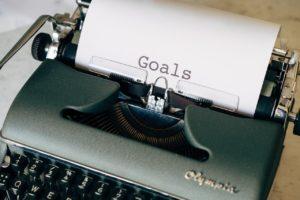 """Une feuille sort d'une machine à écrire ancienne, de couleur verte. On peut voir le titre de la feuille : """"Goals"""""""