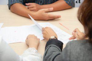 Une table avec des papiers. On voit les mains de trois personnes autour de la table.