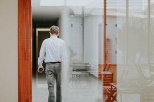 On voit un homme de dos. On le voit à travers une vitre.