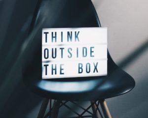 """Une lightbox sur une chaise où l'on voit écrit """"Think outside the box"""""""