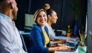 Trois personnes assises l'une à côté de l'autre, face à des ordinateurs. La personne au milieu est une femme et elle sourit à la personne à côté d'elle.