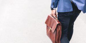 On voit un homme de dos en train de marcher. Il porte un pantalon noir, une veste de costume bleu et il tient à la main une sacoche en cuir marron.