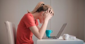 Une femme devant son ordinateur se prend la tête entre les mains. Elle a l'air stressée.