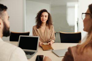 Un entretien d'embauche : une femme est assise en face de deux autres individus à une table.