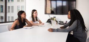 Deux femmes assises à une table face à une troisième femme. Elles sourient.