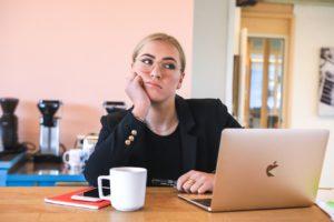 Une femme assise face à son ordinateur. Elle a sa tête posée sur sa main et elle a l'air de s'ennuyer.