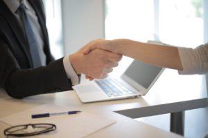 Deux personnes se serrent la main au-dessus d'une table.