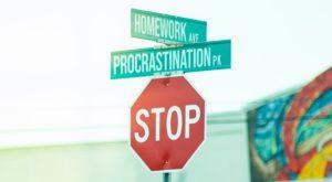 """Un panneau STOP au-dessus duquel il y a deux petits panneaux verts avec écrit """"homework"""" et """"procrastination""""."""