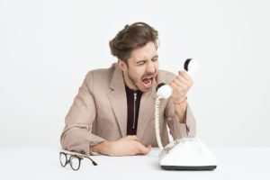 Un homme jeune en costume clair est assis à une table blache. Le fond derrière lui est blanc aussi. Il y a un vieux téléphone blanc sur la table et une paire de lunettes de vues. L'homme tient le récepteur du téléphone à la main et il semble crier sur la personne de l'autre côté du téléphone.