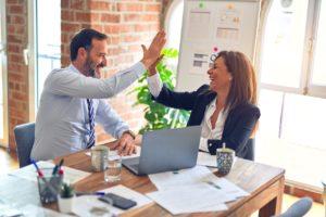 Un homme et une femme sont assis à une table. Ils rigolent et se tapent dans la main en signe de victoire. Sur la table il y a des dossiers et un ordinateur portable.