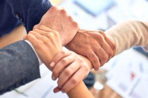4 personnes se tiennent le poignet de sorte à créer un lien en carré.