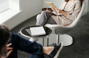 Deux personnes assises l'une en face de l'autre avec une table basse entre eux. L'une d'elles est assise avec les jambes croisées et des papiers à la main. L'autre personne est assise un peu plus nonchalamment et est en train de parler.