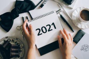 Un bureau avec un café, des papiers, des stylos, etc. On voit des mains qui tiennent un calendrier avec écrit 2021.