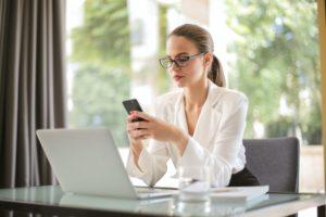 Une femme assise devant un bureau face à un ordinateur portable ouvert. Le fond est une fenêtre et on voit la nature à l'extérieur. Elle porte des lunettes, une queue de cheval et une chemise blance. Elle tient un téléphone portable à hauteur de ses yeux et elle semble envoyer un SMS.
